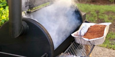 smoker-emitting-smoke-with-large-brisket-ready-to-DMZ456B-1-min-1